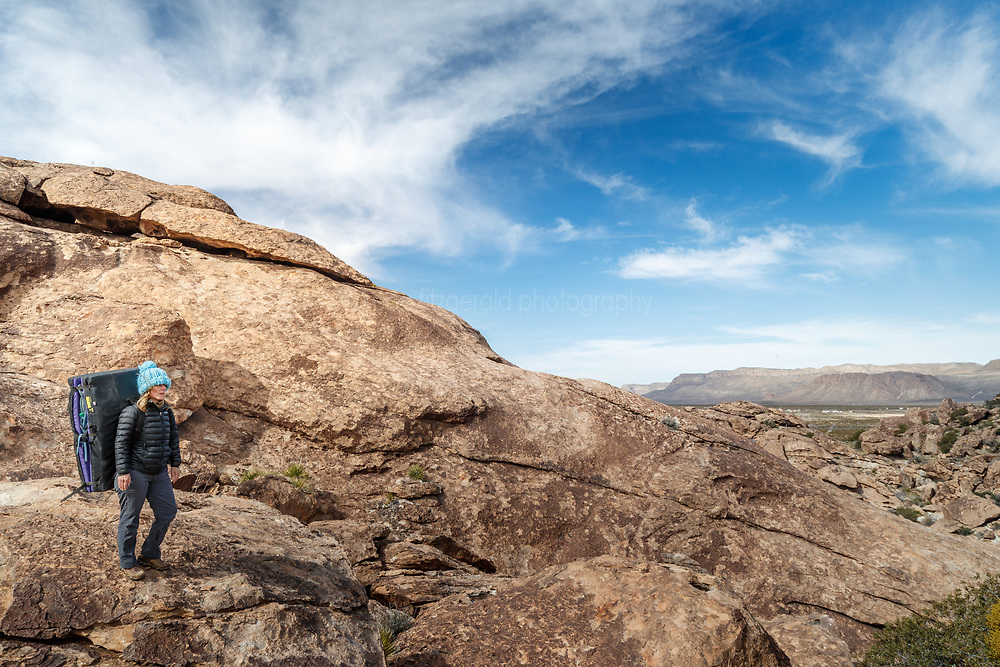 Sarah Hepola carrying bouldering pads to climbing site, Hueco Tanks State Park & Historic Site, El Paso, Texas. USA.