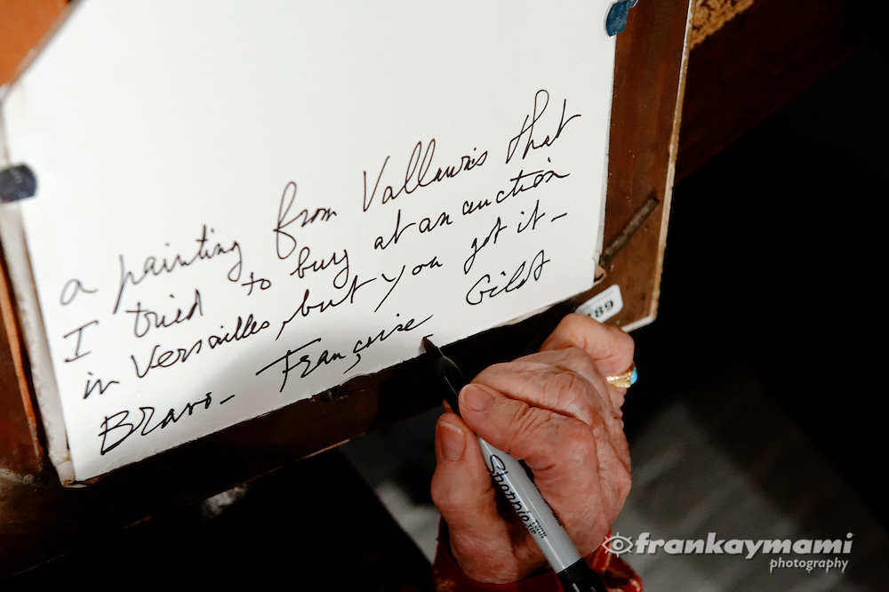 Artist Françoise Gilot signs the back of a painting for an art collector during an opening at Vincent Mann Gallery in New Orleans, LA.