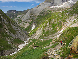 Woman hiking in the High Pyrenees descending from Hourquette d'Ossoue to the valley Barranque d'Ossoue, Gavarnie, France