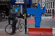 The back of a road crossing figure and a cyclist at the junction of Oxford Street and Tottenham Court Road. During the extensive construction of the capital's Crossrail transport project, street-level disruption has been massive and pedestrians and drivers have endured re-routing and hold-ups for many years. On the other side of these blue signs are human figures that stand at these junctions to stop crossing on red lights and thereby help stop accidents.