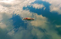 July 19, 2017 - Zixing, China - Clouds are reflected as a boat floats on the Xiaodong Jiang river in Zixing, central China's Hunan Province.  (Credit Image: © Cao Zhengping/Xinhua via ZUMA Wire)