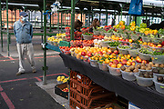 With new local coronavirus lockdown measures now in place and Birmingham currently set at 'Tier 2' or 'high', people wearing face masks shopping at the open fruit and vegetable market in the city centre on 14th October 2020 in Birmingham, United Kingdom. This is the first day of the new three tier system in the UK which has levels: 'medium', which includes the rule of six, 'high', which will cover most areas under current restrictions; and 'very high' for those areas with particularly high case numbers. Meanwhile there have been calls by politicians for a 'circuit breaker' complete lockdown to be announced to help the growing spread of the Covid-19 virus.