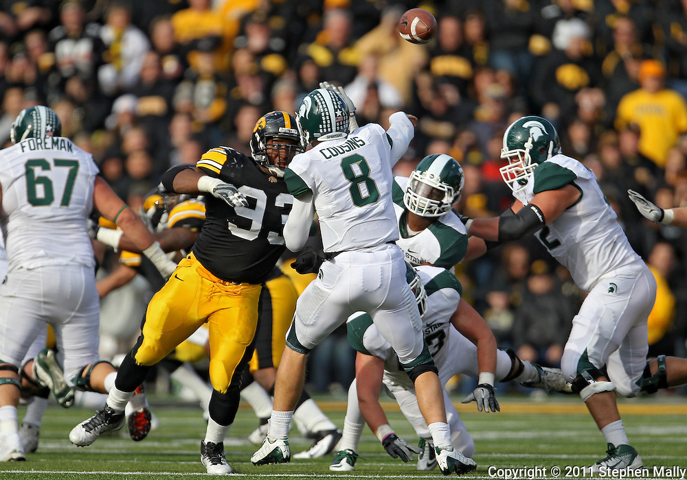 November 12, 2011: Michigan State Spartans quarterback Kirk Cousins (8) passes the ball as Iowa Hawkeyes defensive lineman Mike Daniels (93) closes in during the second half of the NCAA football game between the Michigan State Spartans and the Iowa Hawkeyes at Kinnick Stadium in Iowa City, Iowa on Saturday, November 12, 2011. Michigan State defeated Iowa 37-21.