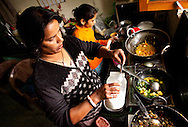 Maya Rai (left), the head cook at Astitva, and Kamlesh Chandra (right) the assistant cook, work together to prepare a hot lunch in the kitchen at Astitva, a non-profit organization in Dehradun, India. Food from the kitchen is served to the day-school children, staff and to customers who buy traditional Indian tiffins for lunch. Astitva, a non-governmental organization (NGO), helps battered women become more economically independent, such as starting small businesses. It also provides the women with family services so they have time to pursue their business interests. The kitchen at Astitva is operated by two women as a profit-making business. Dehradun is a city of 575,000 about six hours north of New Delhi by train. Nestled next to the Himalayan foothills, it's a little off the path for most tourists. Astitva is located in a neighborhood where poor and upper class people live within close proximity.