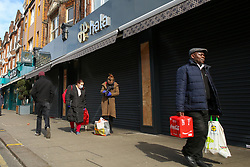 © Licensed to London News Pictures. 21/03/2020. London, UK. People walk past a closed restaurant in Green Lanes, Haringey, north London. The closures follow Prime Minister, BORIS JOHNSON'S request that all restaurants, cafes and pubs should close until further notice as the Coronavirus impact worsens. Photo credit: Dinendra Haria/LNP