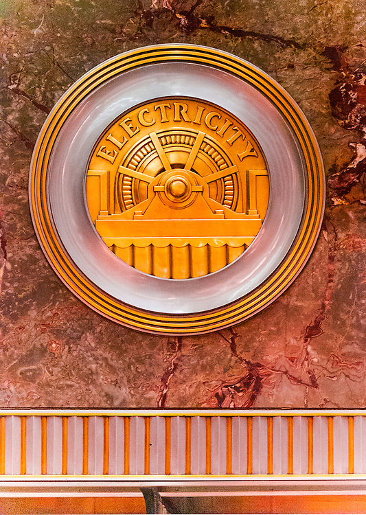 A machine-age, Art Deco, brass medallion, or roundel, on the Empire State Building's marble-walled lobby -- one of 11 such roundels, each honoring a different technology or craft essential to the construction of the great building. This one celebrates electricity.