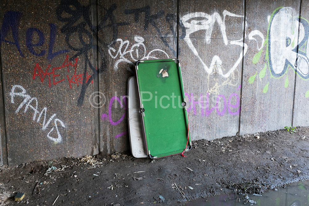 Discarded snooker table against a graffiti covered wall on waste land. London, UK.