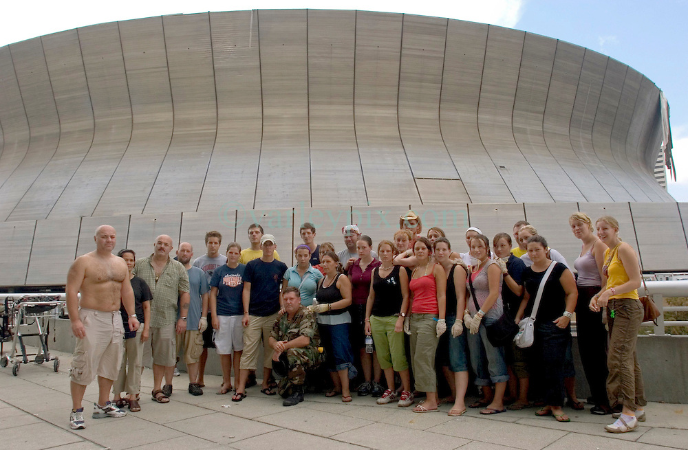 31st August, 2005. 'Hell on earth.' The Superdome in New Orleans, Louisiana where over 20,000 refugees from hurricane Katrina are crammed into hellish conditions. British tourists trapped by the storm pose with Staff Sgt Garland Ogden - their saviour. Ogden pulled them out of the hell that is the Superdome.