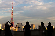 Asian tourists take photo and selfies in front of Tokyo Tower from the Roppongi Hills complex, Tokyo, Japan. Thursday December 5th 2019