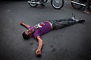 A man is lying injured in the middle of the street, after having been hit at the neck during a scuffle, in Bhopal, Madhya Pradesh, India, near the abandoned Union Carbide (now DOW Chemical) industrial complex.