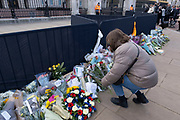 Woman lays a floral tribute of condolence following the death of Prince Philip, Duke of Edingburgh outside Buckingham Palace on 11th April 2021 in London, United Kingdom. Members of the public have been laying flowers outside the gates of the royal residence following his passing at the age of 99 on 9th April 2021. Prince Philip, Duke of Edinburgh was a member of the British royal family as the husband of Elizabeth II. Philip was born into the Greek and Danish royal families.