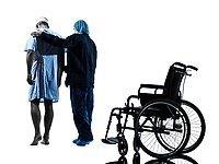 one injured man walking away from wheelchair with nurse in silhouette studio on white background