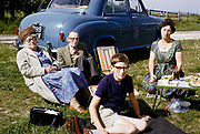 Family picnic in the countryside sitting on grass by car, South Downs, West Sussex, England photographed in 1962