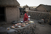 A women walks past bowls of potatoes, barley grain, clay, cheese - parts of the traditional diet in the Altiplano region - in the courtyard of a mud and thatch roof farm near Puno, Peru.