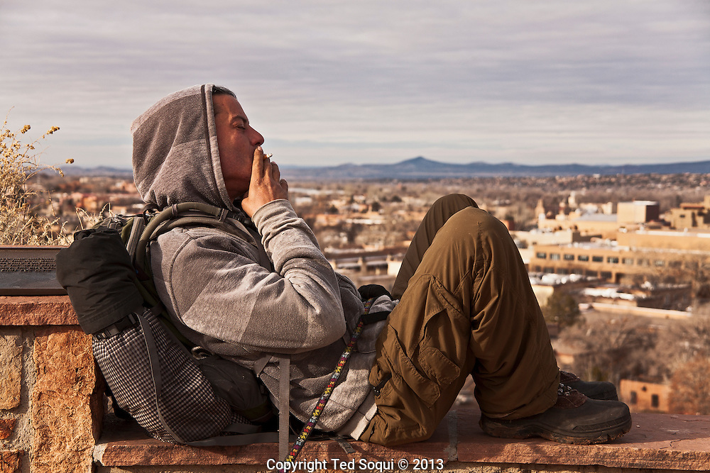 Winter in New Mexico..A young traveller rest on a hill above the city of Santa Fe, New Mexico.