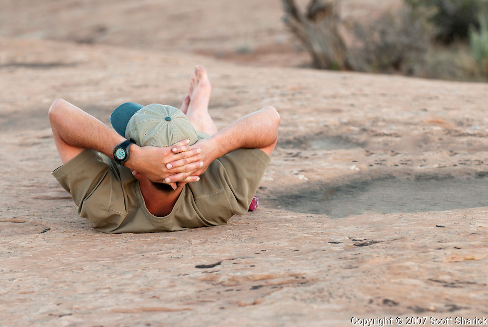 A man lays on a rock in the desert to rest. Missoula Photographer