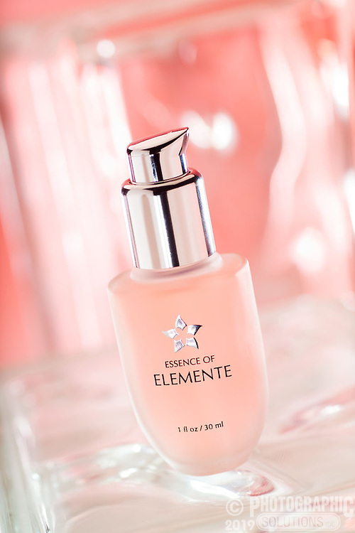 Facial serum shot on a series of glass blocks with different colors behind. This one is pink to match the product