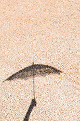 Shadow on rock of an arm holding up an umbrella