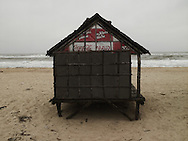 Small stilt house on a beach in Quang Binh province, viet nam, asia. Top of the cabin is closed with a tarpaulin printed with coca cola logo