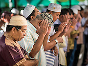 17 JULY 2015 - BANGKOK, THAILAND:     Men pray at Ton Son Mosque during services marking Eid al-Fitr. Eid al-Fitr is also called Feast of Breaking the Fast, the Sugar Feast, Bayram (Bajram), the Sweet Festival or Hari Raya Puasa and the Lesser Eid. It is an important Muslim religious holiday that marks the end of Ramadan, the Islamic holy month of fasting. Muslims are not allowed to fast on Eid. The holiday celebrates the conclusion of the 29 or 30 days of dawn-to-sunset fasting Muslims do during the month of Ramadan. Islam is the second largest religion in Thailand. Government sources say about 5% of Thais are Muslim, many in the Muslim community say the number is closer to 10%.          PHOTO BY JACK KURTZ