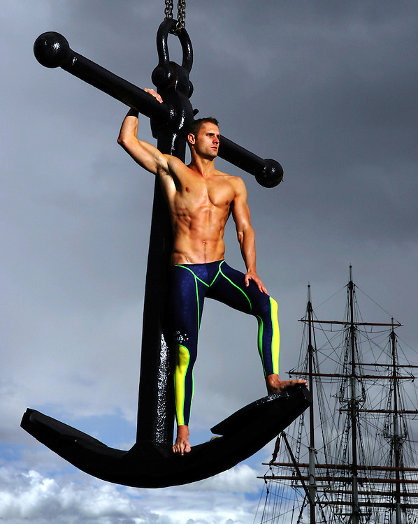 Australian swimmer Brett Hawke was at his chiseled best leading into the 2006 Commonwealth Games and I was keen to nab him for a portrait to run as a sport cover.<br /> With a crane hoisting Hawke no less then five metres high off the ground, he posed bravely on an old fashion anchor down in front of the historic Polly Woodside ship.<br /> One Elinchrome light used on full power hits him hard from a scaffold we got built for the shoot. (Copyright Michael Dodge/Herald Sun)