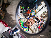 20 APRIL 2013 - BANGKOK, THAILAND:   A boy reflected in the mirror of a motor scooter in Talat Noi (Talat means Market, Noi means Small. Literally Small Market). The Talat Noi neighborhood in Bangkok started as a blacksmith's quarter. As cars and buses replaced horse and buggy, the blacksmiths became mechanics and now the area is lined with car mechanics' shops. It is one the last neighborhoods in Bangkok that still has some original shophouses and pre World War II architecture. It is also home to a  Teo Chew Chinese emigrant community.   PHOTO BY JACK KURTZ