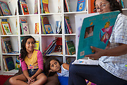 Giovana Lima do Rosa (left) and Ketlin Raissa Azevedo Trindade  (right) sit on colourful cushions listening to a story in the community library, Biblioteca Comunitaria do Arquipelago, Porte Alegre, Brazil. <br />