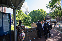 London, June 14th 2017. A fire rages through a residential tower block, Grenfell Tower, in Kensington, West London, with the entire building engulfed in flames. More than 200 firefighters are attending the incident and there are reports of people trapped inside. No figures are available as to casualties. People on a nearby housing estate watch the drama unfold.