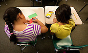 Aubrey Aguila and Elizabeth Gallegos, left and right, work on a writing assignment in Ms. Bergen's third grade class at Bennion Elementary School in Salt Lake City, Monday, Dec. 17, 2012.