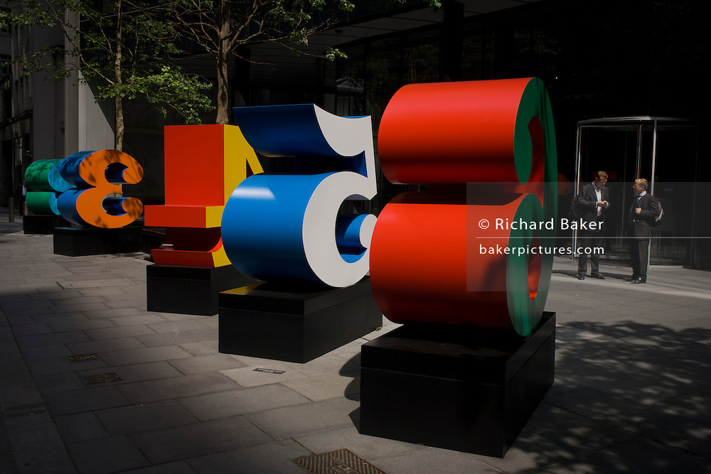 City workers talk near an art installation entitled 'One Through Zero (The Ten Numbers)' by American pop artist Robert Indiana (b 1928), in Lime Street, City of London, the capital's Square Mile, and its financial heart.