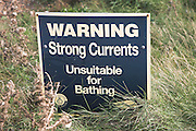 Sign saying Warning Strong Currents Unsuitable for Bathing