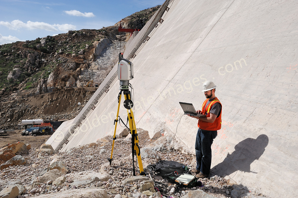 Surveyor using HDS equipment to survey San Vicente Dam.    <br /> <br /> San Vicente Dam completed in 1943, is owned and operated by the San Diego County Water Authority. <br /> <br /> An impressive renovation is currently underway. The existing dam is 220 feet high and will be replaced by a new dam, built at its face. The new dam will rise 117 feet above the top of the current spillway and increase the total reservoir storage capacity from 90,000 acre feet of water to 152,000 acre feet. <br /> <br /> This is a photo taken during an HDS survey of the existing dam.