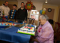 """Helen Clark """"Big Gram"""" receives a birthday cake in honor of her 100th birthday with her grandson Scott Clark and great grand children Brady and Colby in the family room at Genesis Rehab in Laconia on Sunday afternoon.    (Karen Bobotas/for the Laconia Daily Sun)"""