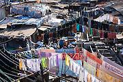 Indian hand laundry, Dhobi Ghat, and laundrymen with traditional flogging stones to wash clothing at Mahalaxmi, Mumbai, India