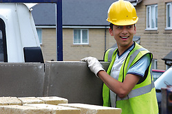 Trainee builder working on Housing Association houses as part of Go for It training programme opportunity for young ethnic people to enter construction industry UK