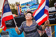 24 JANUARY 2014 - BANGKOK, THAILAND: An anti-government protestor waves Thai flags near the Victory Monument Shutdown Bangkok protest site. Shutdown Bangkok has been going for 12 days with no resolution in sight. Suthep Thaugsuban, the leader of the anti-government protests and the People's Democratic Reform Committee (PDRC), the umbrella organization of the protests,  is still demanding the caretaker government of Prime Minister Yingluck Shinawatra resign, the PM says she won't resign and intends to go ahead with the election.    PHOTO BY JACK KURTZ