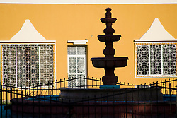 Mexico, Yucatan, Valladolid, La Parraquia de San Servacio church, fountain and yellow walls of house