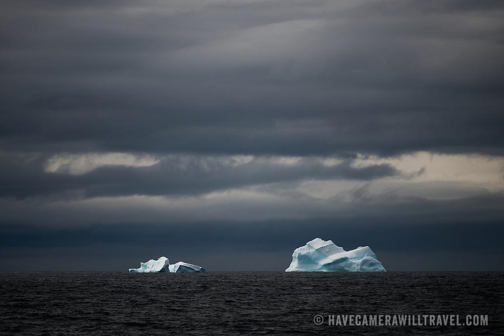 Two blue icebergs float on the horizon against dark skies in Antarctica.