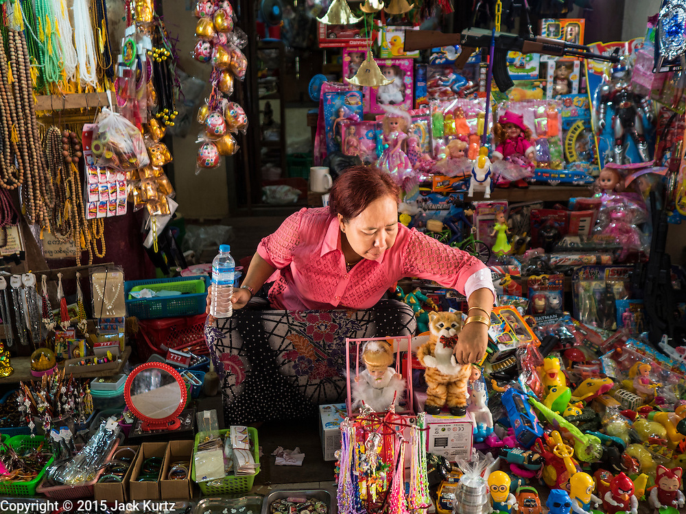 30 OCTOBER 2015 - TWANTE, MYANMAR:   A toy vendor selling all sort of children's toys including toy guns, in the main entrance to the Shwe San Taw Pagoda (Paya) in Twante, also spelled Twantay. The pagoda was established more than 2500 years ago, although constantly rebuilt and renovated. According to Burmese history and local legend, the pagoda houses eight hairs from Gautama, the historical Buddha. PHOTO BY JACK KURTZ
