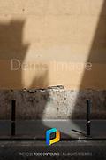 Shadows falling on a sidewalk in Rome, Italy.
