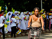 27 NOVEMBER 2017 - YANGON, MYANMAR: A man rides his bike past Burmese waiting to see Pope Francis. Pope Francis arrived in Yangon Monday for a four day / three night visit. Tuesday he is going to the capitol, Naypyidaw (Nay Pyi Taw) to meet with Aung San Suu Kyi and other Myanmar leaders. Wednesday and Thursday he is saying mass in Yangon and on Thursday afternoon he is going to neighboring Bangladesh. There are around 450,000 Catholics in Burma, about 1% of the total population.   PHOTO BY JACK KURTZ