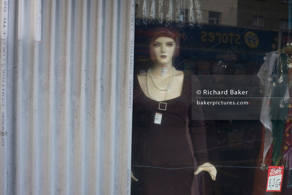 Corrugated sheeting and a staring mannequin clothes model in Camden London, a victim of the UK recession.