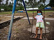 """22 JANUARY 2018 - GUINOBATAN, ALBAY, PHILIPPINES: A girl at Muladbucad Grande Elementary School in Guinobatan wears a face mask while she plays on the swings. Several communities in Guinobatan were hit ash falls from the eruptions of the Mayon volcano and many people wore face masks to protect themselves from the ash. There were a series of eruptions on the Mayon volcano near Legazpi Monday. The eruptions started Sunday night and continued through the day. At about midday the volcano sent a plume of ash and smoke towering over Camalig, the largest municipality near the volcano. The Philippine Institute of Volcanology and Seismology (PHIVOLCS) extended the six kilometer danger zone to eight kilometers and raised the alert level from three to four. This is the first time the alert level has been at four since 2009. A level four alert means a """"Hazardous Eruption is Imminent"""" and there is """"intense unrest"""" in the volcano. The Mayon volcano is the most active volcano in the Philippines. Sunday and Monday's eruptions caused ash falls in several communities but there were no known injuries.    PHOTO BY JACK KURTZ"""