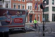 A TFL Santander bike engineer and a scene of bikes, on 11th January 2017, in Mayfair, London, England.