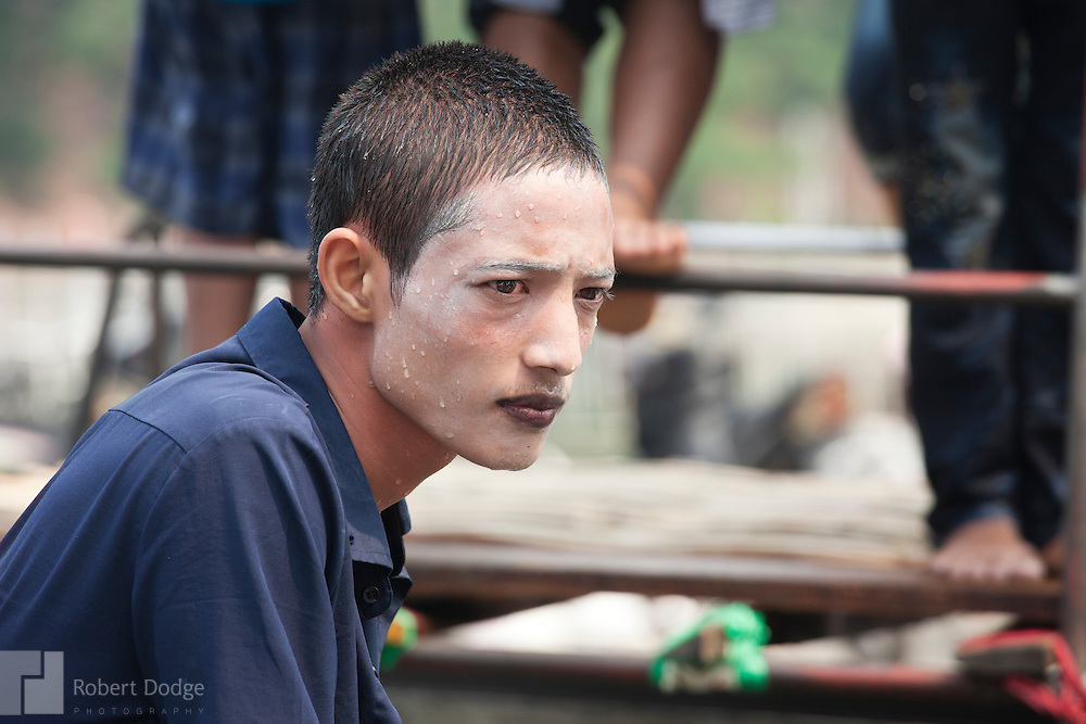 Mandalay, Myanmar- April 14, 2013: A young man takes a break from the festivities and partying during Myanmar's Thingyan Water Festival. Thingyan is held in April, one of the hottest months of the year in Myanmar. The water festival marks the country's New Year celebration and the festival includes lots of drinking, singing, dancing and theater. Wherever you are you are likely to get doused with water as the Burmese see this as a cleansing of the previous year's sins and bad luck and a blessing for good luck and prosperity in the year ahead. In the major cities of Mandalay and Yangon, large platforms are erected along major roadways and are equipped with high powered water hoses. The platforms, sponsored by large corporate donors, also have dance stages and play the latest pop and hip hop music. Thousands of residents pour into the streets by foot, motorbike and flatbed truck to get hosed under the platforms while they drink and dance. Many of the young celebrants wear their best clubbing clothes. And many of the party goers are men, having left their wives and girlfriends at home.
