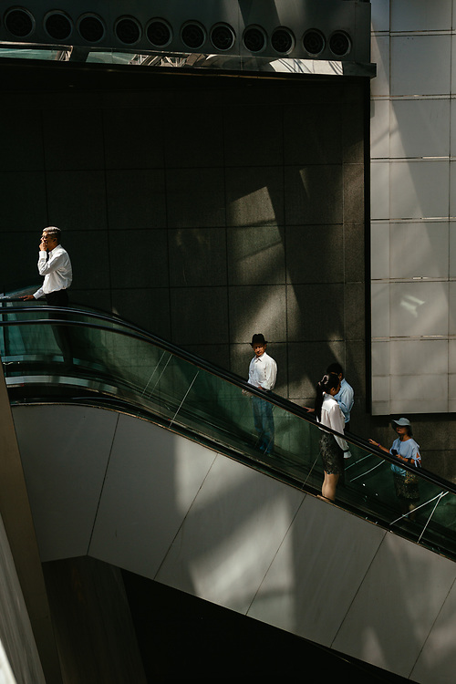 People ride an escalator at an office building in Central, Hong Kong Island, on October 15, 2019.