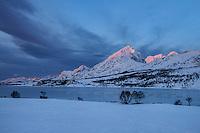 First light illuminating Ristind mountain peak, Vestvågøy, Lofoten Islands, Norway