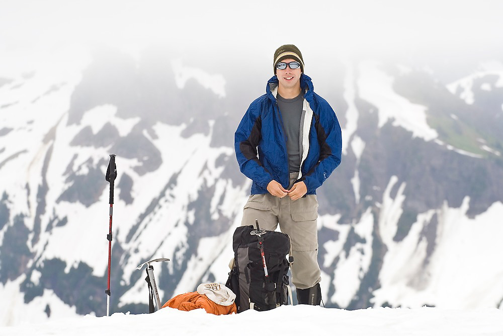 Brian Polagye zips up his jacket after a short snack break during an ascent of Tomyhoi Peak, Mount Baker Wilderness, Washington.