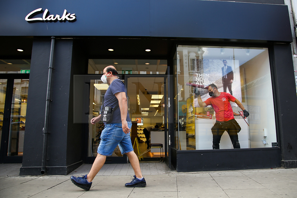 © Licensed to London News Pictures. 13/06/2020. London, UK. A man wearing a face covering walks past as a cleaner cleans the window of Clarks store in Wood Green, north London as the store prepares to re-open on Monday. The government has announced that all non-essential retailers can re-open on Monday 15 June as the coronavirus lockdown restrictions are eased. Photo credit: Dinendra Haria/LNP