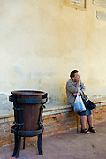 Elderly lady stops for a rest by Piazza Pio II after shopping in the market in Pienza, Tuscany, Italy